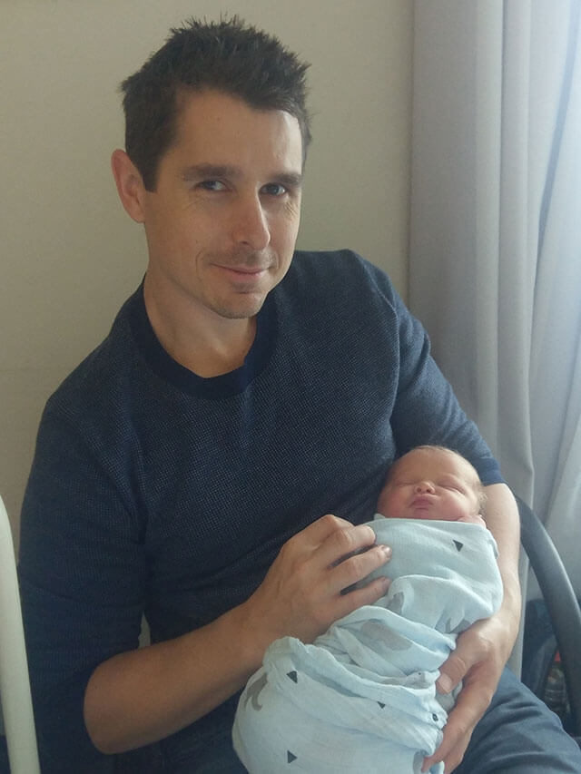 Adrian holding his son, Lachlan